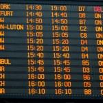 Flights information board in an international airport terminal — Stock Photo
