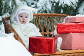 Christmas baby with gift on vinewoven bench — Stok fotoğraf