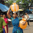 Stock Photo: MUMBAI, INDI- NOVEMBER 26: Indiwomcarry water jugs in In