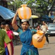 MUMBAI, INDIA - NOVEMBER 26: Indian woman carry water jugs in In - Stok fotoğraf