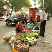 MUMBAI, INDIA -NOVEMBER 26: Unidentified vendors sell goods in a vegetable street market on Nov. 26, 2010 in Mumbai, India. Agricultural sector makes up 18.1% of GDP. India is the biggest producer of — Stock Photo