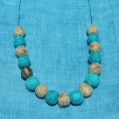 Felt and metal necklace on turquoise linen background — Stock Photo