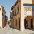 Stock Photo: Street with arcades and murals in Dozz, Italismall town kno