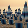 Scene with closed blue and white striped beach umbrellas and de — Stock Photo