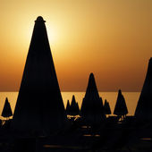 Silhouettes of many furled beach umbrellas on the beach on sunse — Stock Photo