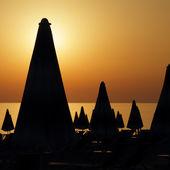 Silhouetten van vele furled strand parasols op het strand op sunse — Stockfoto