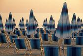 Scène met gesloten blauw en wit gestreept strand parasols en de — Stockfoto
