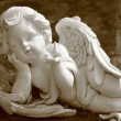 Little angel with butterfly, statue in sepia — Stock Photo
