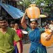 Indian woman carry water jugs — Stock Photo