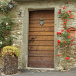Front door decorated with climbing roses in old tuscan village,  — Stock Photo