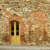 Old brick and stone wall with door to the tuscan house, Anghiari — Stock Photo
