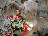 Angelic sculpture with flowers — Stock Photo