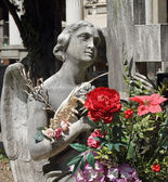 Angel statue with bouquet of flowers on tomb — Stock Photo