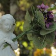 Little angel figure holding a huge bouquet of flowers — Stock Photo #33658665