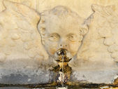 Old public drink water source with angelic decoration — Stock Photo