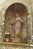 Shrine with Madonna figure and lily in pot in niche on wall — Stock Photo