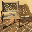 Stock Photo: Openwork chair on brick paved floor