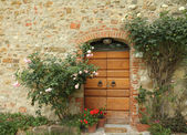 Doorway decorated with climbing roses — Stock Photo