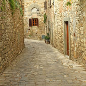 Narrow paved street and stone walls in italian village — Stock fotografie