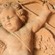 Antique relief of cupid with arrow and bow — Stock Photo