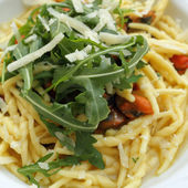 Pasta trofie with clams and decorated with rucola and parmesan — Stock Photo