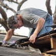 Man Examining and Repairing Leaking House Roof — Stock Photo #16970143