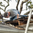 Stock Photo: Man Examining and Repairing Leaking House Roof