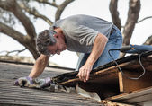 Man Examining and Repairing Leaking House Roof — Foto de Stock