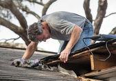 Muž zkoumání a opravit děravou střechu domu — Stock fotografie