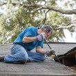 Man Repairing Leaking Roof - Stock Photo
