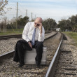 Tired Jobless senior businessman sits on suitcase on railroad train tracks — Stock Photo