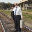 Stock Photo: Angry, jobless senior businessmwalking along railroad train tracks