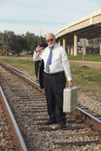 Angry, jobless senior businessman walking along railroad train tracks — Stock Photo
