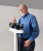 Senior Male on Weight Scale Holding Up One Finger — Stock Photo