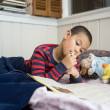 School age Boy Reading in Bed with Workbook - Stock Photo