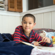 Royalty-Free Stock Photo: Grade school Age Boy Reading in Bed with Workbook