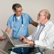 Senior Medical Doctors Discussing Patients MRI Film Scans - Stock Photo