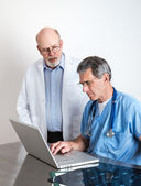 Senior Medical Doctors Discussing Patient's MRI Film Scans — Stock Photo