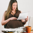 Stock Photo: Pregnant Young WomReading Overdue Bills At Laptop Computer