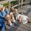 Seniors birdwatching and relaxing on old wooden foot bridge — Stock Photo
