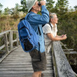 Senior Couple Hiking and Birdwatching on Old Wooden Foot Bridge — Stock Photo