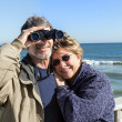 Retired senior couple on Florida beach vacation hugging and birdwatching — Foto de Stock
