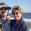 Retired couple on beach vacation birdwatching with binoculars — Foto de Stock