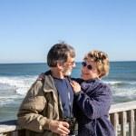 Retired senior couple hugging on sunny Florida fishing pier — Foto de Stock
