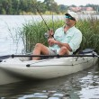 Man Fishing in Kayak in shallow reeds and grasses — Stock Photo #48218491