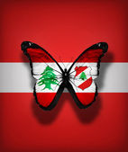 Lebanese flag butterfly with emblem, isolated on flag background — Zdjęcie stockowe