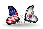 две бабочки с флагами на крылья, как символ отношений сша и южная корея — Стоковое фото