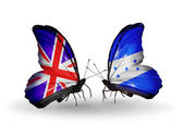 Two butterflies with flags on wings as symbol of relations UK and Honduras — Stock Photo