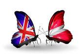 Två fjärilar med flaggor på vingarna som symbol för förbindelserna mellan förenade kungariket och lettland — Stockfoto