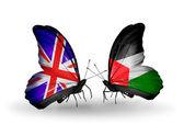 Dva motýli s příznaky na křídlech jako symbol vztahů, Velké Británii a v Palestině — Stock fotografie